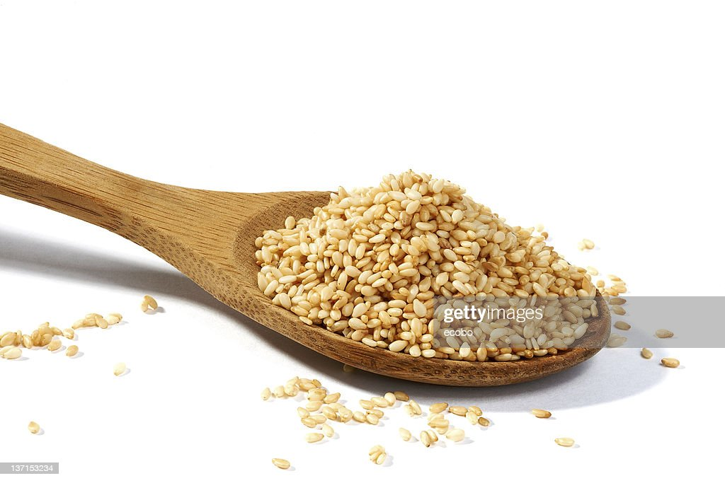 Sesame grains in large wooden spoon : Stock Photo