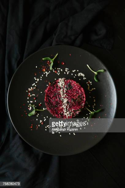 Sesame seeds and garnish on red food on plate