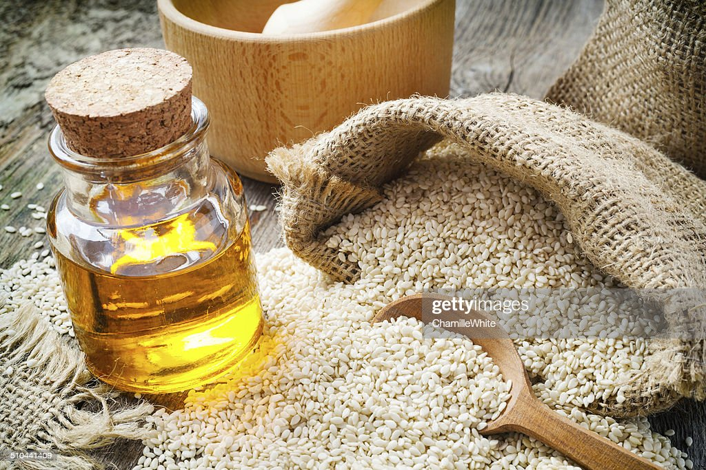 sesame seeds in sack and bottle of oil on  table : Stock Photo