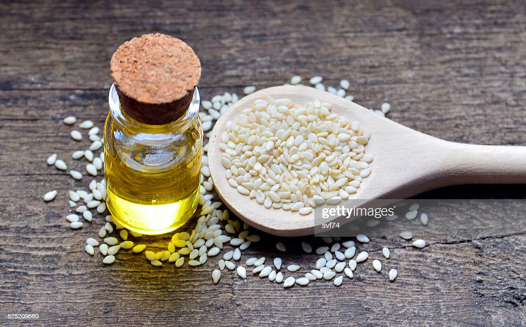 Sesame seeds on wooden spoon and sesame oil. : Stock Photo