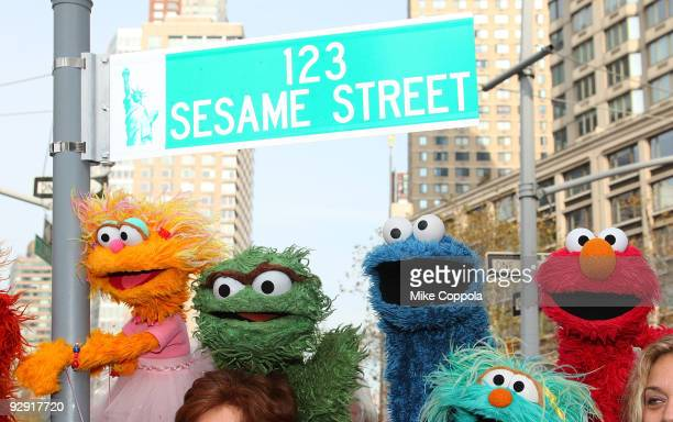 """Sesame Street characters pose under a """"123 Sesame Street"""" sign temporarily renaming the street at the """"Sesame Street"""" 40th Anniversary temporary..."""
