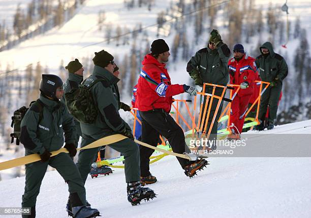 """Members of the Italian """"Truppe Alpine"""" and volunteers carry a hose uphill 07 February, 2006 before injecting a freezing solution into the Giant..."""