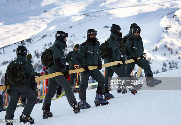 """Members of the Italian """"Truppe Alpine"""" carry a hose uphill 07 February, 2006 to inject a freezing solution into the Giant Slalom skiing run in..."""