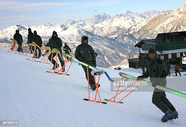 """Members of the Italian """"Truppe Alpine"""" connect a hose 07 February, 2006 to inject a freezing solution into the Giant Slalom skiing run in Sestriere,..."""