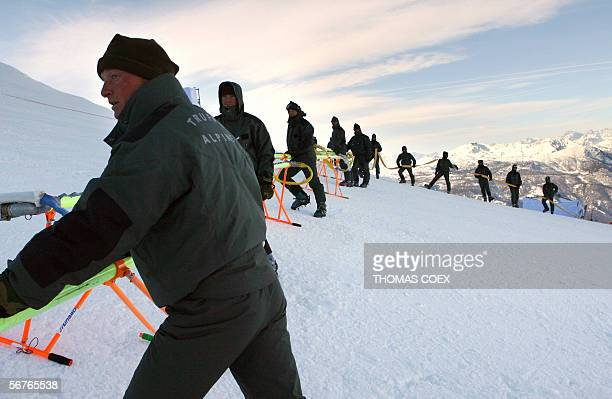 """Members of the Italian """"Truppe Alpine"""" connect a hose 07 February, 2006 before injecting a freezing solution into the Giant Slalom skiing run in..."""