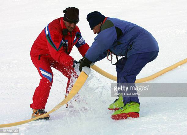 Workers connect a hose 07 February, 2006 before injecting a freezing solution into the Giant Slalom skiing run in Sestriere, Italy, during final...