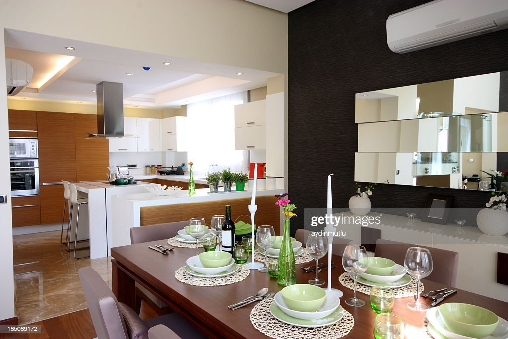 Set dining room table next to kitchen in open concept home : Stock Photo
