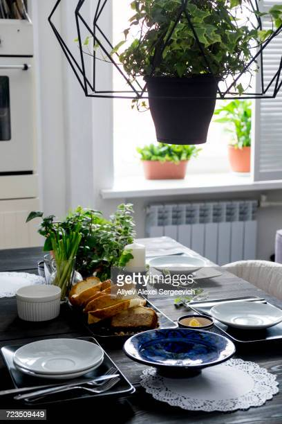 set kitchen table with bread slices, fresh herbs and spring onions - hanging basket stock pictures, royalty-free photos & images