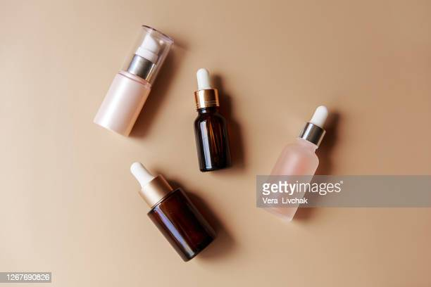 set of amber glass cosmetic bottles on brown background. pump bottle, dropper bottle, dispenser cosmetic container flat lay, top view. - brown hair photos et images de collection