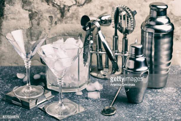 Set of bar tools for making a cocktails arranged on a stone background.
