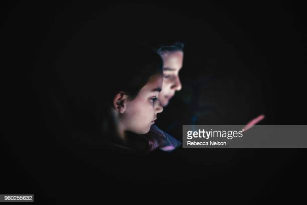 set of boy and girl twins using digital tablets in dark room at night - sister stock pictures, royalty-free photos & images