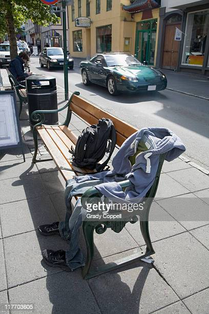 Set of clothes 'seated' on bench on city street