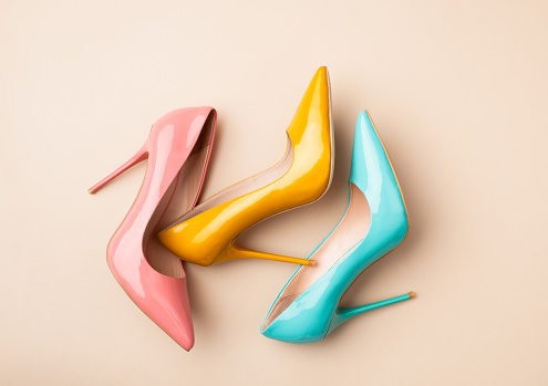 Set of colored women's shoes on beige background 942926448