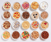 set of different cereals with milk on a white background
