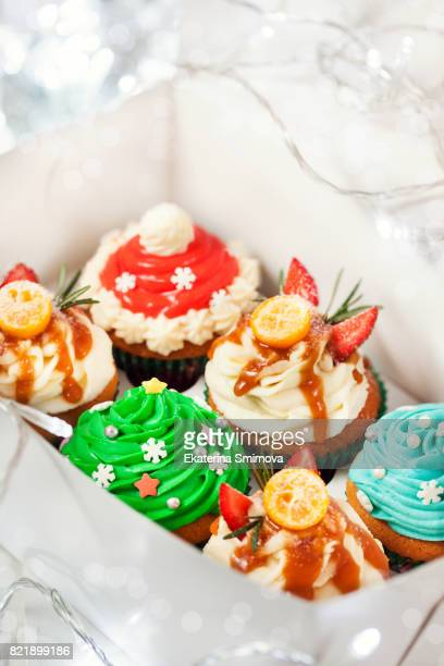 Set of different delicious Christmas cupcakes in a box