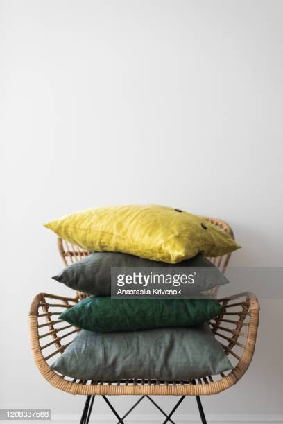 set of folded green and yellow pillows on a armchair. - cushion stock pictures, royalty-free photos & images