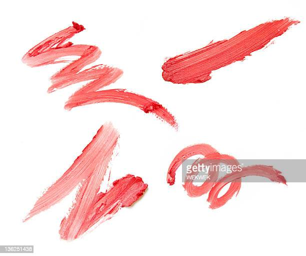Set of four red lipstick smears on white background