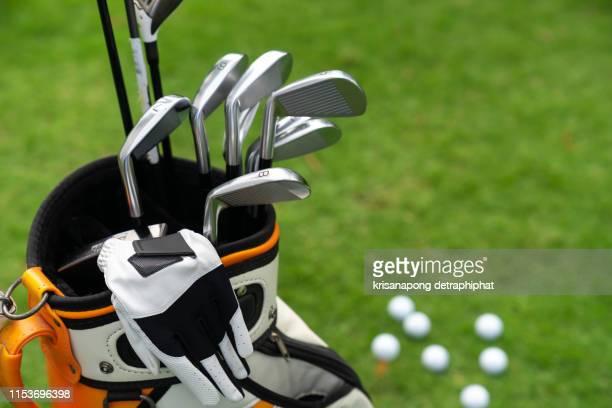 set of golf clubs over green field background,olf clubs drivers over green field background - einlochen golf stock-fotos und bilder
