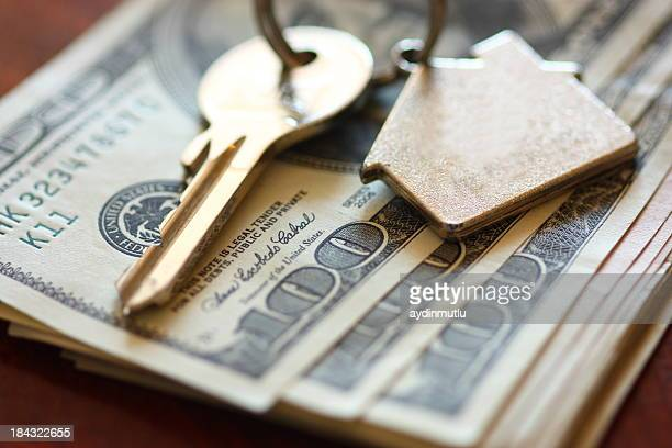 Set of house keys laying on hundred dollar bills