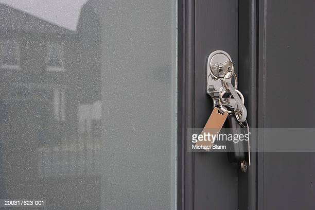 Set of keys hanging from lock on front door, close-up