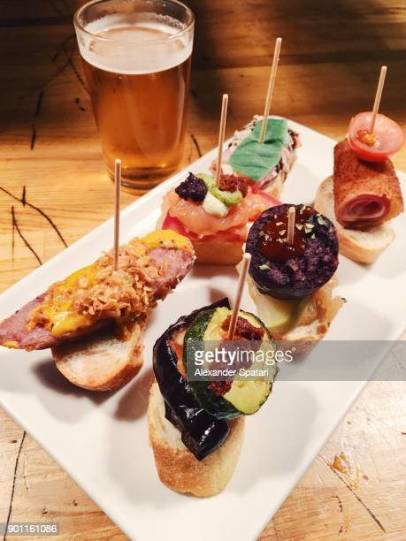 set of pinchos tapas and beer in a bar in barcelona, spain - tapas stock photos and pictures