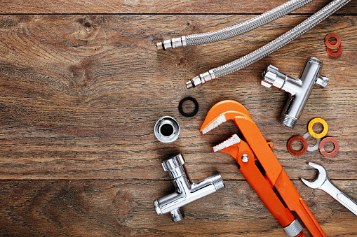 Set of plumbing tools on wooden table background. 1153465197
