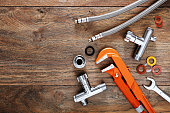 Set of plumbing tools on wooden table background.