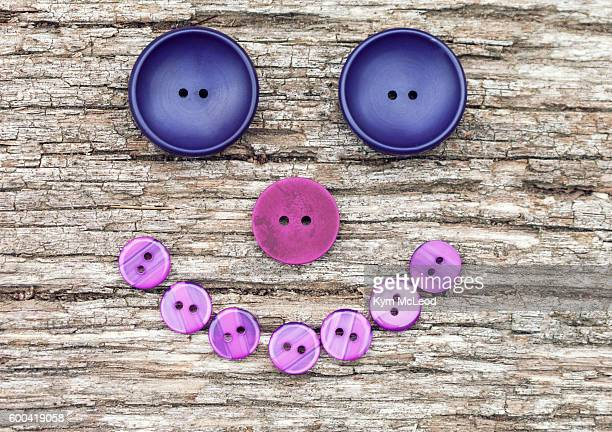 Set of purple and pink buttons in the shape of a smiling face