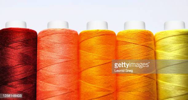 set of spools of red, yellow and orange threads front view close-up macro on white background - embroidery stock pictures, royalty-free photos & images