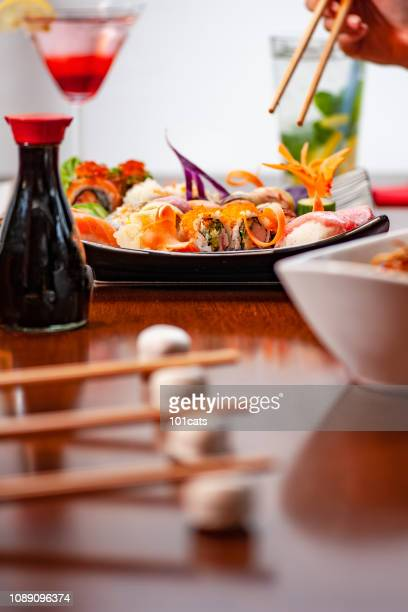 Set of sushi, soy sauce and red wine on food table in sushi restaurant