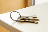Set of three house keys on the ring on table in a room. Bunch of apartment keys close-up. To forget keys at home consept.