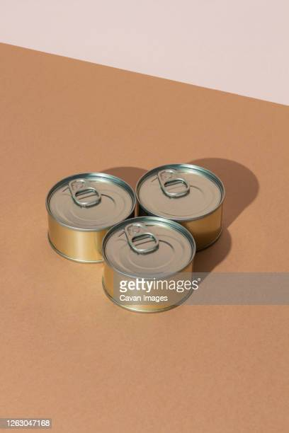 set of tins with canned food on brown surface - tin can stock pictures, royalty-free photos & images