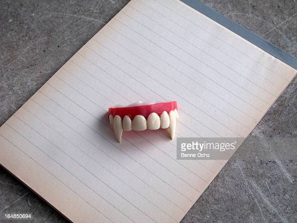 A set of vampire fangs on top of a note pad of lined paper