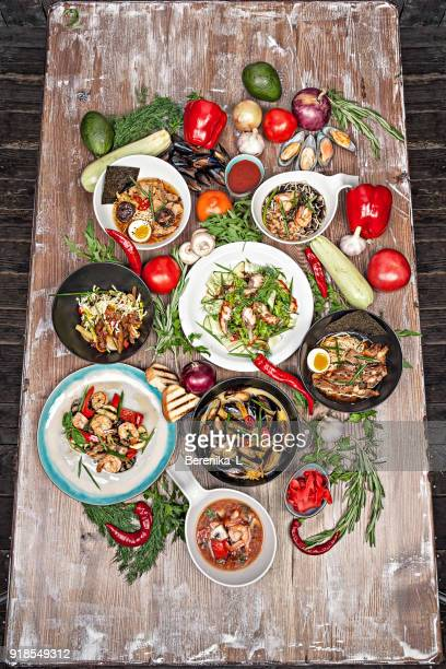 set of various asian dishes , vegetables and herbs on a wooden table. - abundance stock pictures, royalty-free photos & images