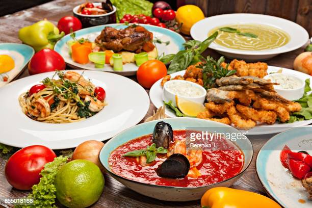 Ensemble de divers plats de la cuisine méditerranéenne, les légumes et les herbes sur une table en bois
