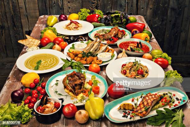 set of various dishes of mediterranean cuisine, vegetables and herbs on a wooden table - abundance stock pictures, royalty-free photos & images