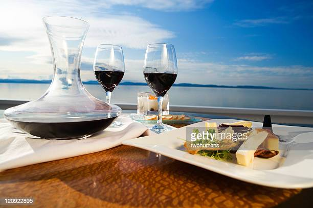 Set table with gourmet appetizer and two glasses on red wine