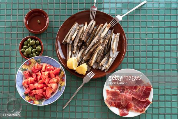 set table with grilled razor clams, fresh tomatoes, olives and iberian ham - dorte fjalland imagens e fotografias de stock