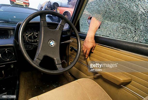 Set up of a man breaking a window in an attempt to steal a BMW February 1992 Car crime twoc twocker twocking criminal criminals broken glass smashed...
