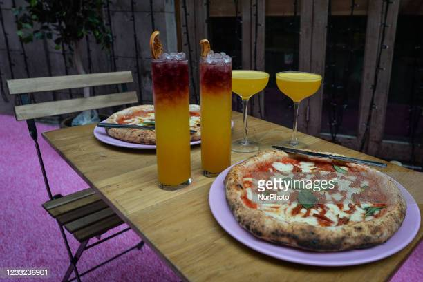 Set with Tropicalia and Porn Star Martini cocktails seen between a Diavola pizza with pepperoni and a Margherita pizza, in front of Pygmalion Bar and...