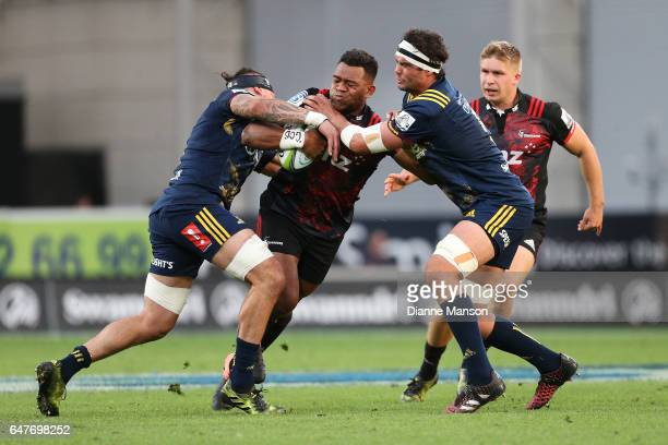 Seta Tamanivalu of the Crusaders tries to break the tackle of Elliot Dixon and Tom Franklin of the Highlanders during the round two Super Rugby match...