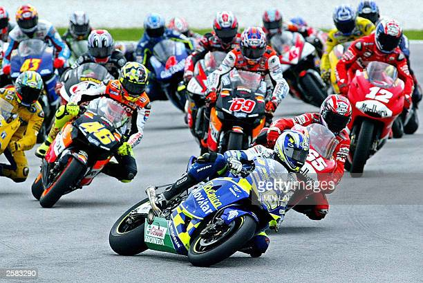Sete Gibernau of Spain leads the pack in his Honda around the first chicane after the start of the Malaysian Motorcycle Grand Prix in Sepang 12...
