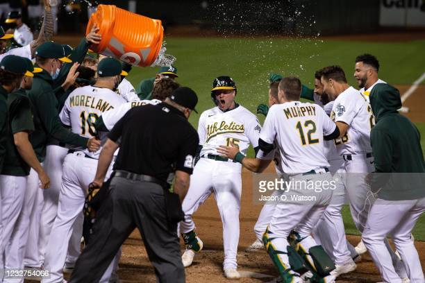 Seth Brown of the Oakland Athletics is congratulated by teammates after hitting a walkoff home run against the Tampa Bay Rays during the ninth inning...