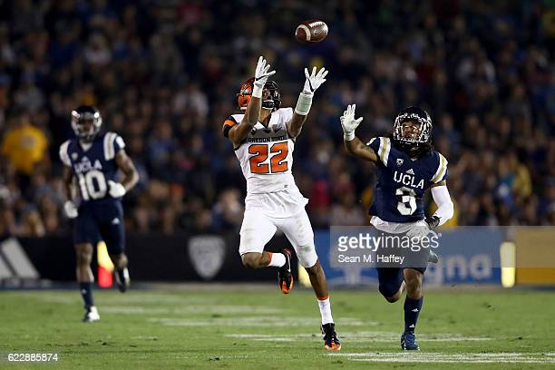 Seth Collins of the Oregon State Beavers catches a pass past the defense of Randall Goforth and Fabian Moreau of the UCLA Bruins during the first...