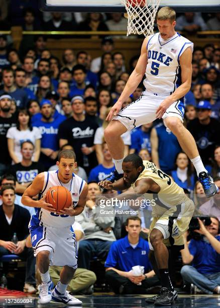 Seth Curry and Mason Plumlee of the Duke Blue Devils battle Travis McKie of the Wake Forest Demon Deacons for a rebound during play at Cameron Indoor...