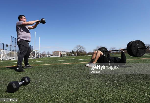 Seth Feld of Oceanside, New York and Dylan Jacobson of Wantagh, New York lift weights at Cedar Creek Park on March 22, 2020 in Seaford, New York....
