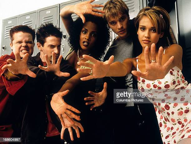 Seth Green Elden Henson Vivica A Fox Devon Sawa and Jessica Alba standing in front of metal lockers as they all extend their hands outward relaying a...