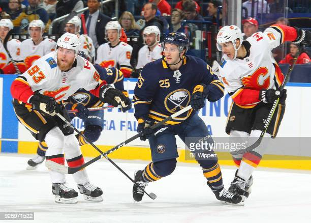Seth Griffith of the Buffalo Sabres skates against Sam Bennett and Travis Hamonic of the Calgary Flames during an NHL game on March 7 2018 at KeyBank...