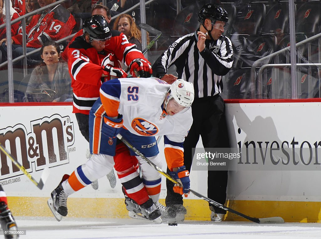 Seth Helgeson #39 of the New Jersey Devils checks Ross Johnston #52 of the New York Islanders at the Prudential Center on October 5, 2016 in Newark, New Jersey.