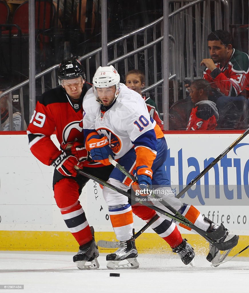 Seth Helgeson #39 of the New Jersey Devils defends against Alan Quine #10 of the New York Islanders at the Prudential Center on October 5, 2016 in Newark, New Jersey.